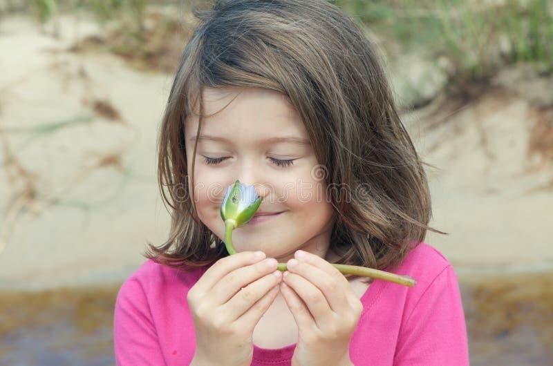 De ruikende bloem van het meisje royalty-vrije stock afbeelding
