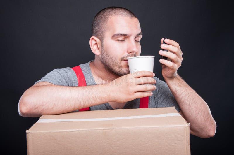 De ruikende koffie die van de verhuizerskerel een onderbreking hebben stock fotografie