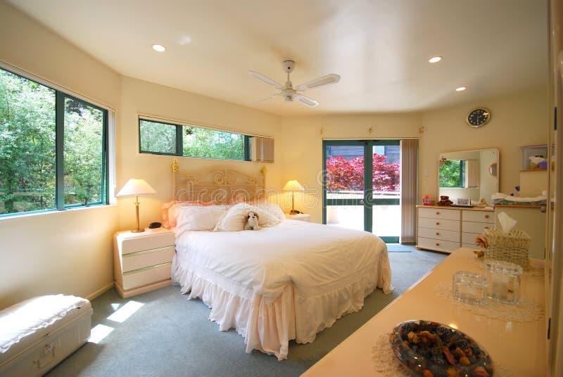 De ruimte van het bed met warme kleurenmuur stock fotografie