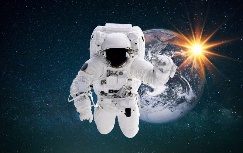 De ruimtevaarder in kosmische ruimte vliegt dichtbij de aarde bij zonsondergang De astronaut voert ruimteopdracht tegen de sterre stock afbeeldingen