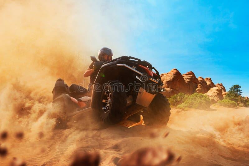 De ruiter die van de vierlingfiets het zand, vooraanzicht beklimmen stock afbeelding