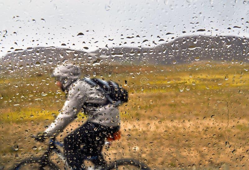 De ruiter van de bergfiets in regen stock afbeeldingen