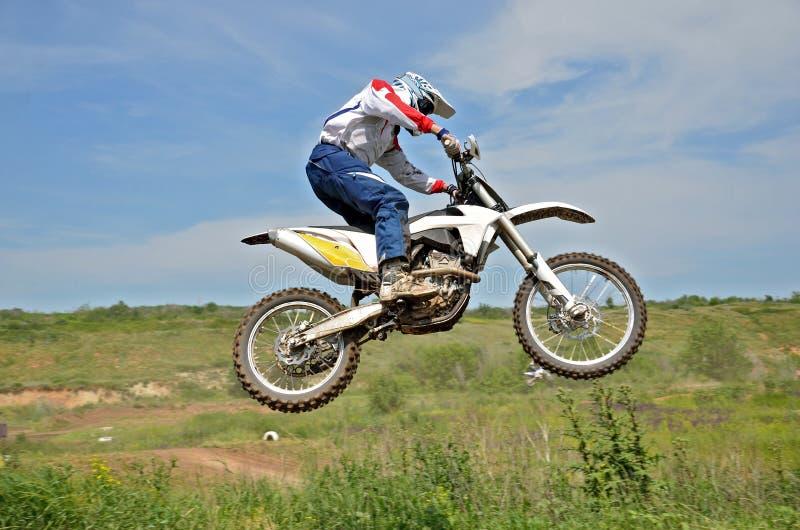 De ruiter van de motocross op een motorfiets in de lucht stock afbeelding