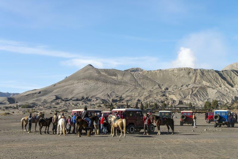 De ruiters bieden paardritten aan reizigers aan bij Onderstel Bromo stock afbeelding