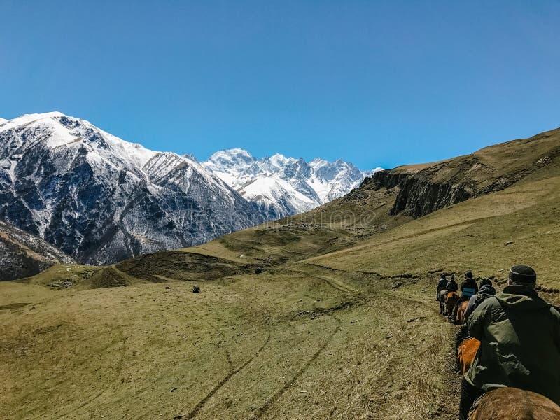 De ruiters op horseback berijden in de bergen tijdens de dag achtermening stock afbeeldingen