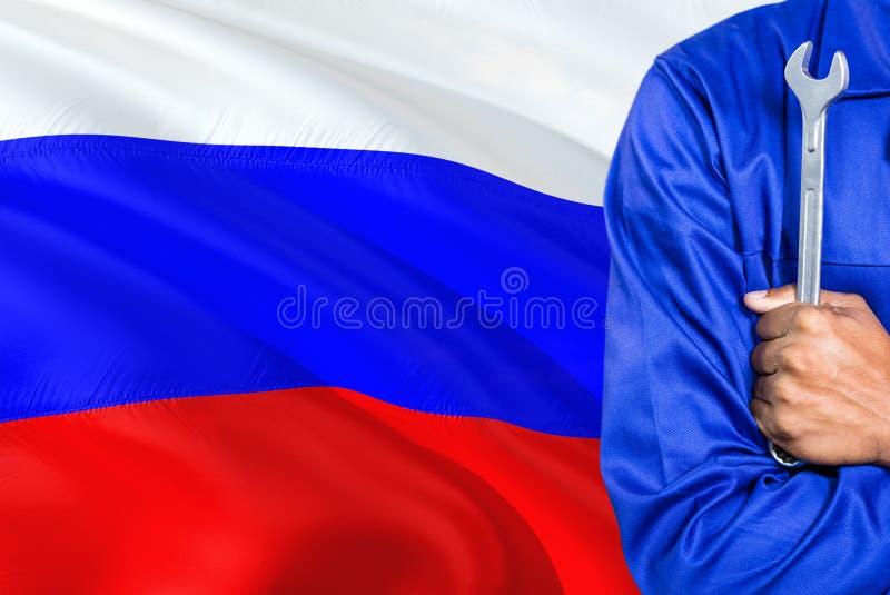 De Russische Werktuigkundige in blauwe eenvormig houdt moersleutel tegen golvende de vlagachtergrond van Rusland Gekruiste wapens stock afbeelding