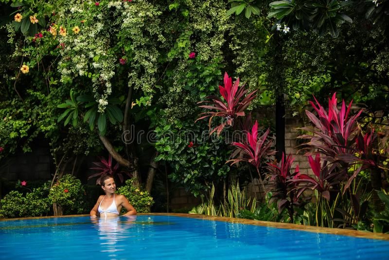 De rust van de Caucasicanvrouw in blauwe pool in keerkringen royalty-vrije stock foto's