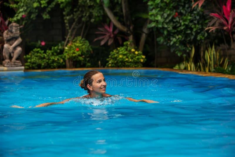 De rust van de Caucasicanvrouw in blauwe pool in keerkringen stock afbeeldingen