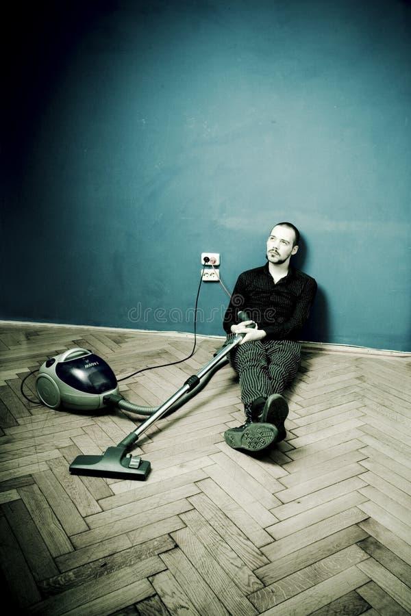 De rust van de kerel op vloer met vacuüm stock foto