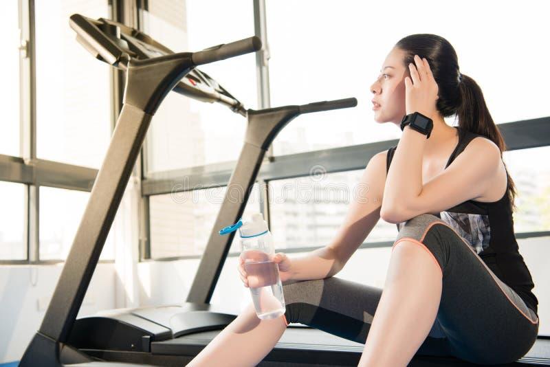 De rust van de sportvrouw op het drinkwater van het tredmolengebruik smartwatch stock foto's