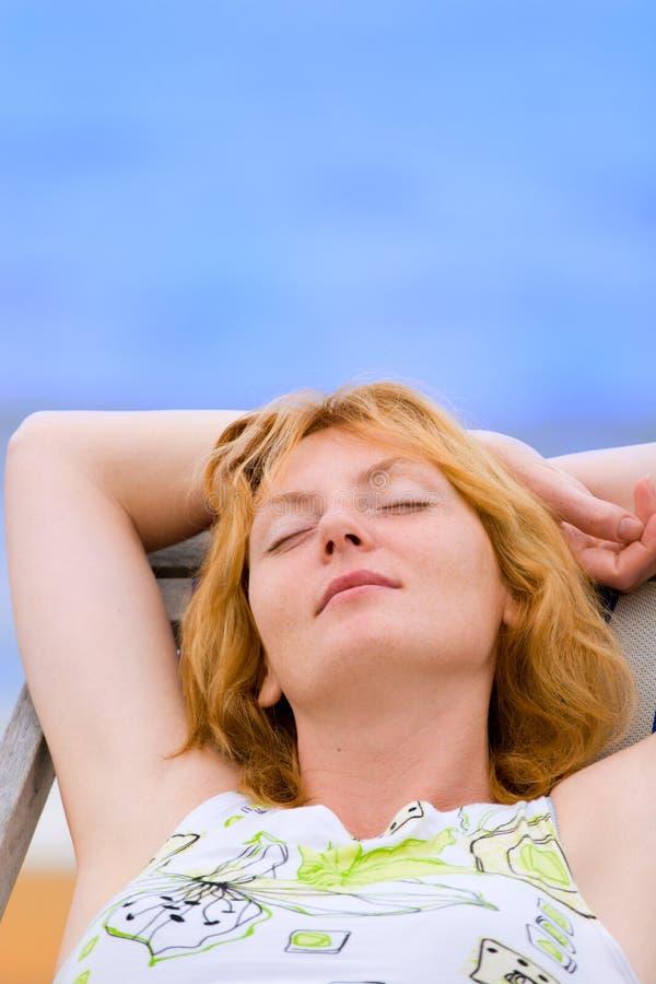 De rust van de vrouw in chaise op overzees strand stock foto's