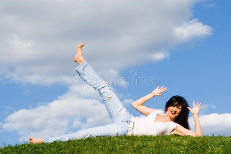 De rust van de vrouw op het groene gras stock fotografie