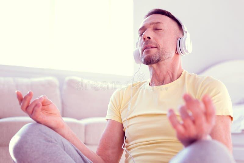 De rust van het mensengevoel en verlicht terwijl zich het mediteren en het concentreren op kalme muziek royalty-vrije stock foto's