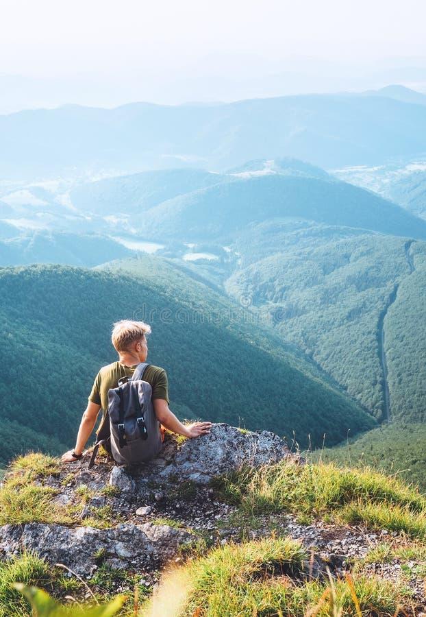 De rust van de jonge mensentoerist op de bovenkant van heuvel met mooie vallei stock afbeelding