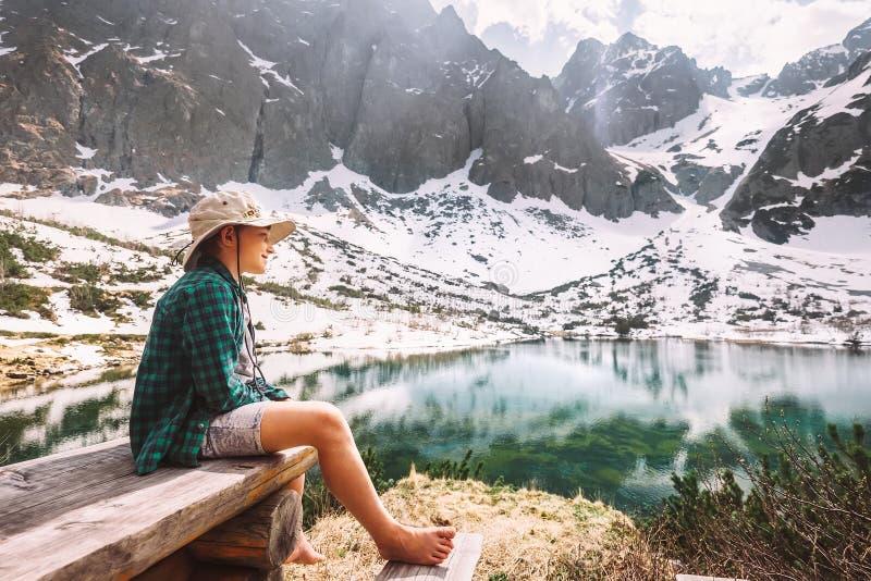 De rust van de jongensreiziger na wandeling dichtbij bergmeer rond sneeuwp royalty-vrije stock afbeeldingen