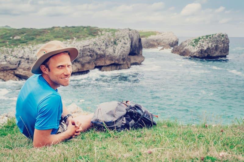 De rust van de mensen backpacker reiziger aan de rotsachtige overzeese kant, kijkt in ca stock fotografie