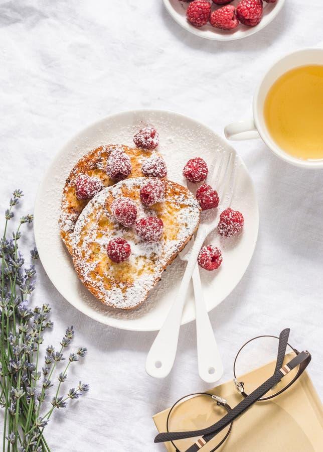 De rust van de middagtheepauze lijst - Franse toost met verse framboos, groen thee en boek op lichte achtergrond, hoogste mening royalty-vrije stock afbeelding