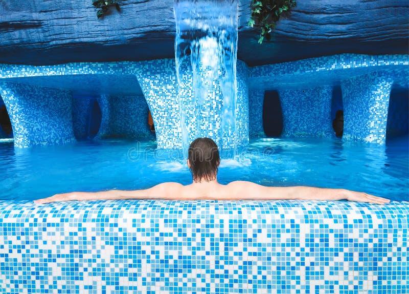 De rustende mens ligt en ontspant in de pool De kerel ontspant in de Jacuzzi Achtermening Volwassen mens die in de pool liggen en royalty-vrije stock afbeeldingen