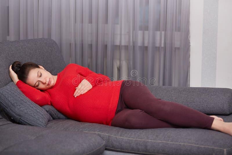 De rustgevende jonge Europese vrouw draagt rode gebreide sweater, beenkappen, ligt op comfortabele bank, houdt handen op buik, vo royalty-vrije stock afbeelding