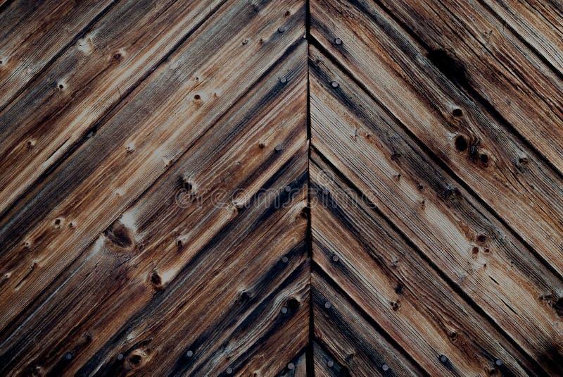 De rustieke donkere antiquiteit bevlekte houten muur met oude, gebarsten houten planken en spijkers in het platteland royalty-vrije stock foto