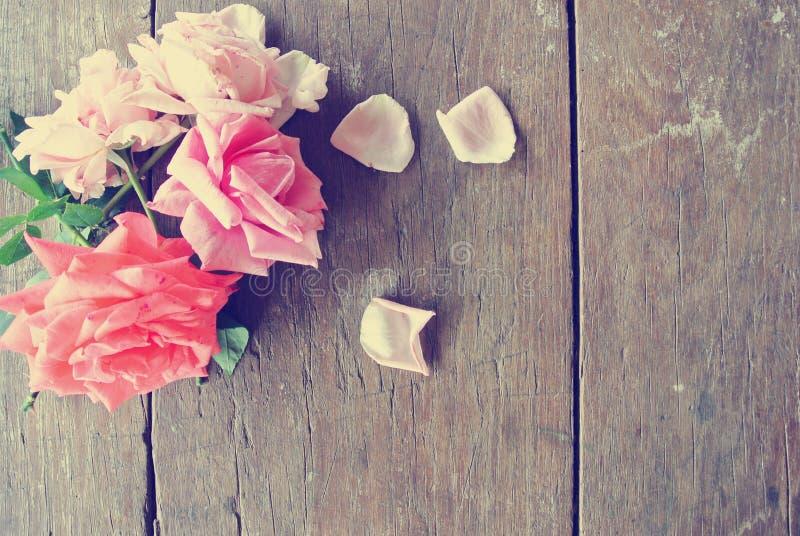 De rustieke houten lijst met roze rozen en nam bloemblaadjes toe stock fotografie
