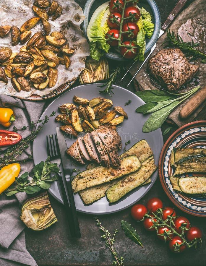 De rustieke maaltijd met geroosterde vlees, aardappelen in de schil en groenten diende op plaat met bestek stock afbeeldingen