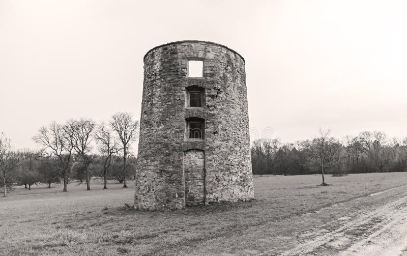 De rustieke oude verlaten silo die van het baksteenlandbouwbedrijf zich op een gebied bevinden stock afbeelding
