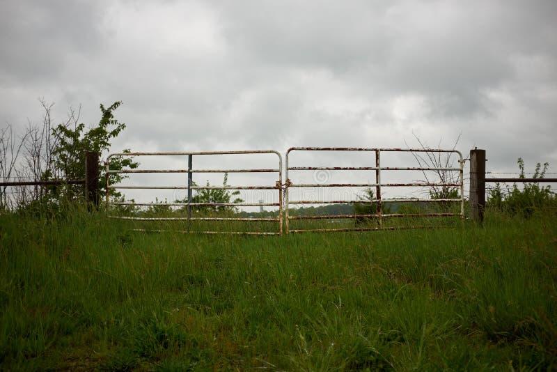 De rustieke poort van het metaallandbouwbedrijf onder een bewolkte hemel stock afbeelding