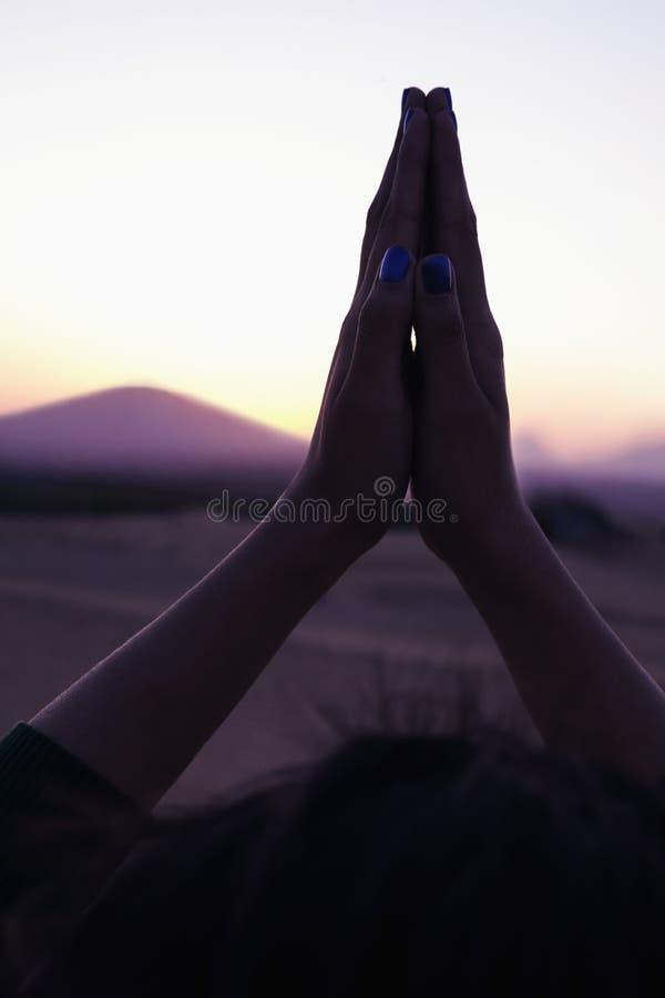 De rustige jonge vrouw met haar palmen in gebed bleef boven haar hoofd in de woestijn in China, close-up bijeen royalty-vrije stock afbeelding