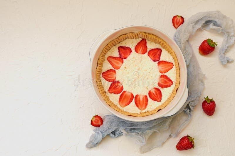 De ruwe aardbeikaastaart in een bakselschotel op de witte achtergrond met exemplaarruimte verfraaide met verse aardbeien royalty-vrije stock afbeelding