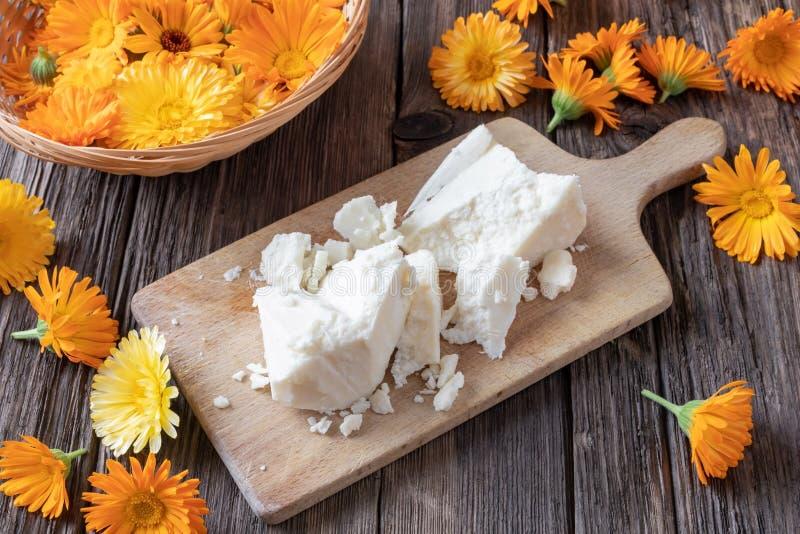 De ruwe bloemen van sheaboom boter en verse calendula stock afbeelding