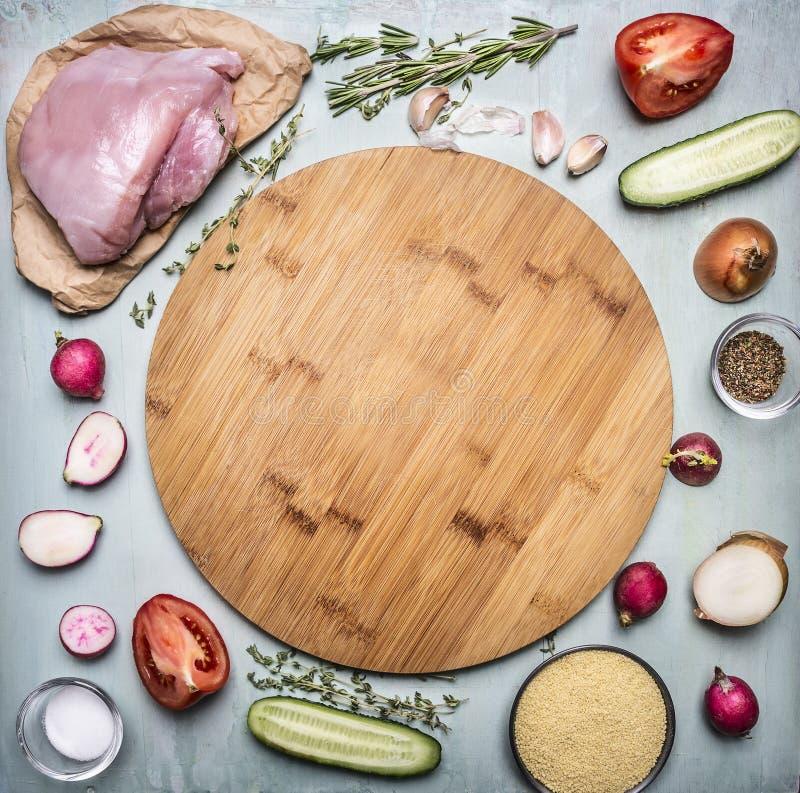 De ruwe borst van Turkije met tomaat en peperradijskruiden en komkommers over houten scherpe raad op rustieke houten hoogste meni stock foto