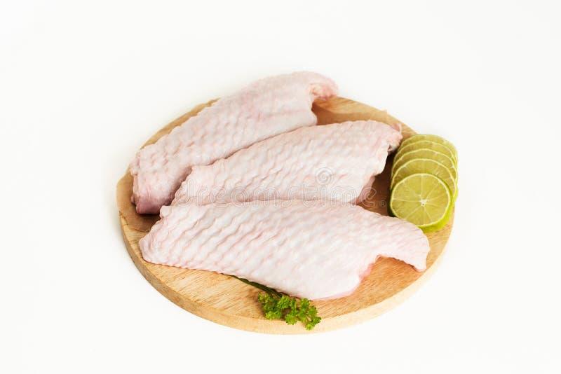 De ruwe delen van de vleugel van Turkije, drie stukken van kip, met kalk en peterselie op een witte achtergrond, isoleren royalty-vrije stock foto