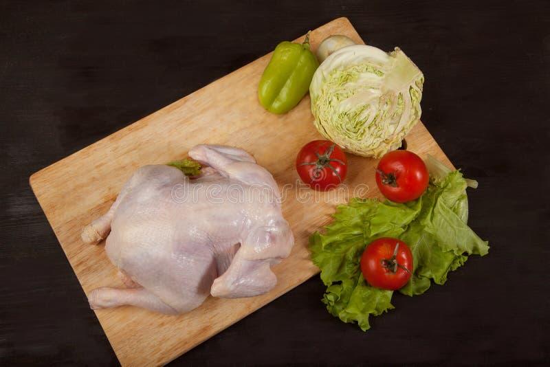 De ruwe gehele kip met rauwe groentenkool, tomaten, sla en peper ligt op een raad op een zwarte achtergrond royalty-vrije stock afbeelding