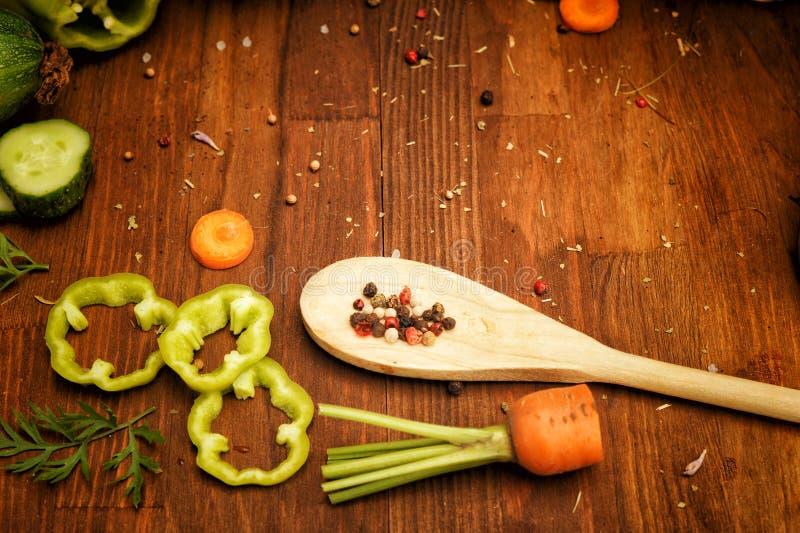 De ruwe gesneden groenten en de kruiden in houten lepel op een uitstekende stijllijst, vlakte lagen royalty-vrije stock foto