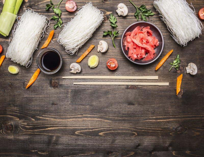 De ruwe glasnoedels met eetstokjes, ui, sla, gember, hakten peper, paddestoelen, gevoerde kader houten rustieke bovenkant als ach stock afbeeldingen