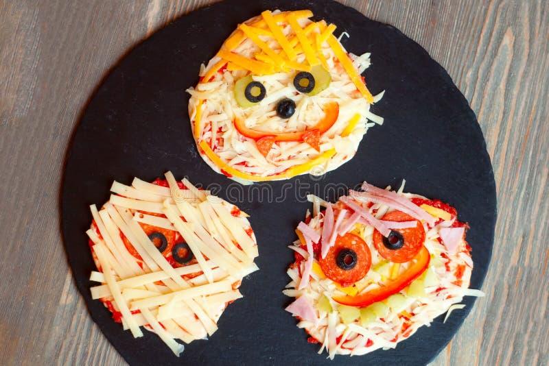 De ruwe Halloween-pizza met monsters, boven scène met decor op een zwarte plaat treft voor gebakken voorbereidingen, idee voor he stock foto's