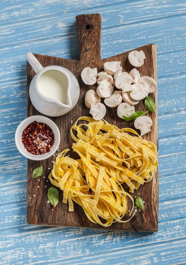 De ruwe ingrediënten voor het koken van deegwaren met paddestoel romen saus af - deegwaren, paddestoelen, room, kruiden stock foto