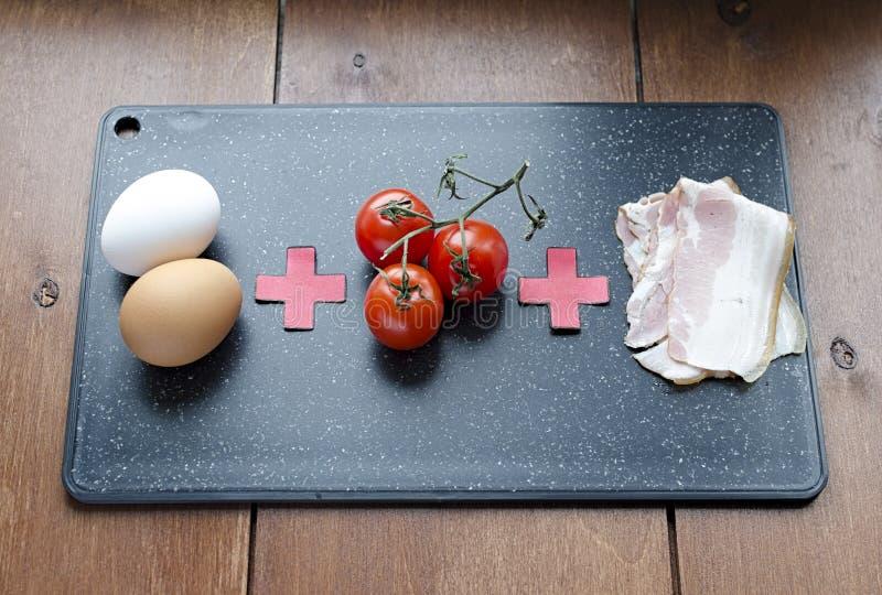 De ruwe ingrediënten voor roereieren, de ruwe voedselformule, de tomateneieren en het bacon op een knipsel schepen mening 45 in stock foto