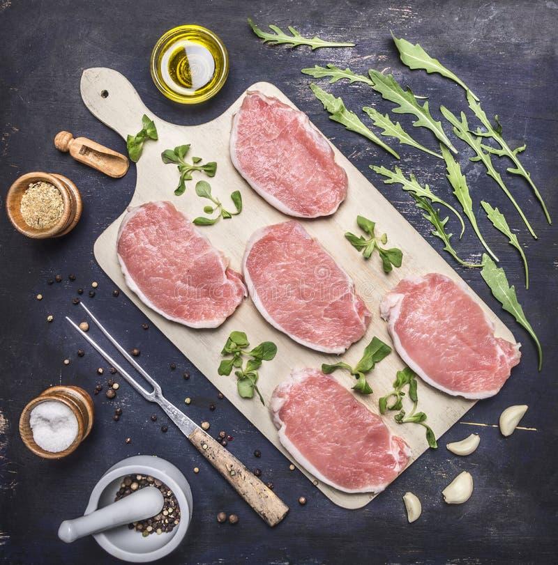 De ruwe lapjes vlees van het Vlees vastgestelde Varkensvlees met kruiden en kruiden op een witte scherpe raads houten hoogste men stock foto's