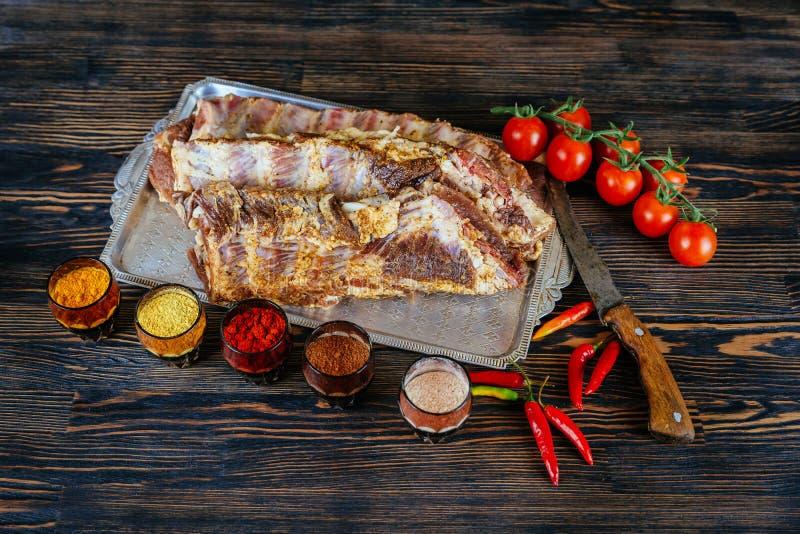 De ruwe ongekookte Varkensvleesribben op houten besnoeiing schepen klaar om zwarte geweven achtergrond te koken in royalty-vrije stock afbeeldingen