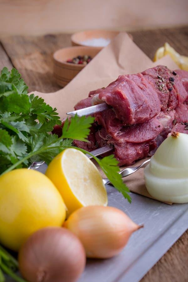 De ruwe rundvleesvleespennen, ongekookte slachterij hakten vlees en kokende ingrediënten op houten lijst stock foto