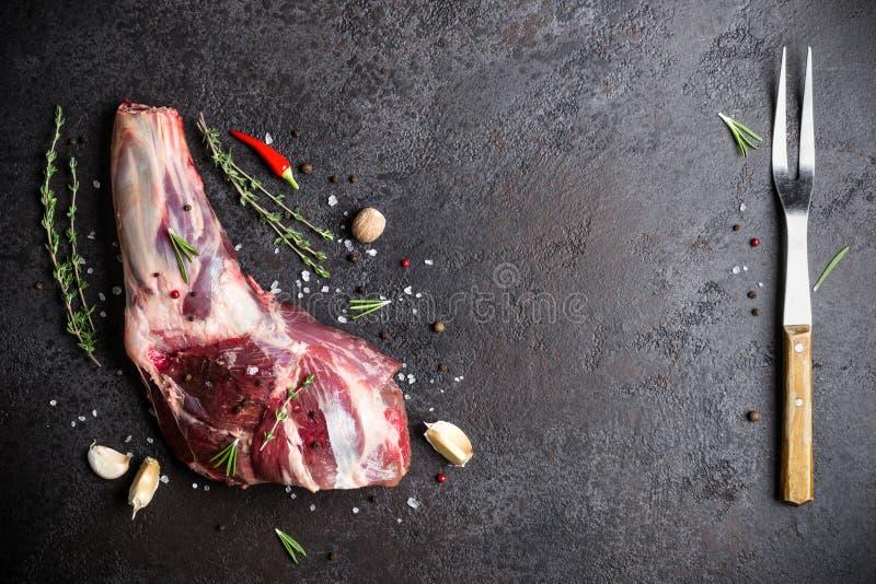 De ruwe verse steel, de kruiden en de vork van het Lamsvlees op zwarte steenachtergrond stock fotografie
