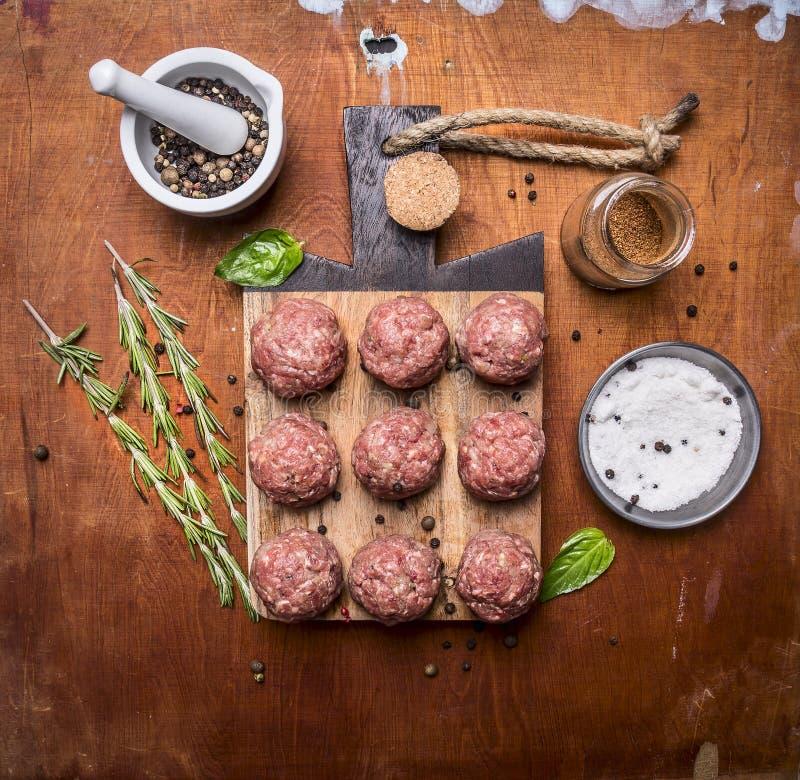 De ruwe vleesballetjes op een scherpe raad met kruiden en kruiden houten hoogste mening rustieke als achtergrond sluiten omhoog royalty-vrije stock afbeelding