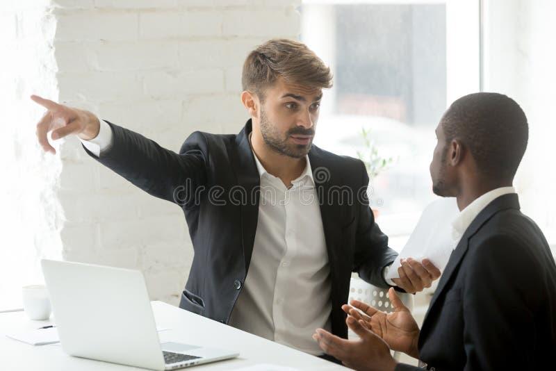 De ruwe witte partner het vertellen zwarte zakenman gaat zijn bureau weg royalty-vrije stock foto's
