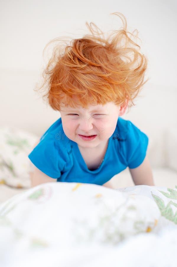 De ruwharige baby ontwaakte enkel in het bed stock foto's