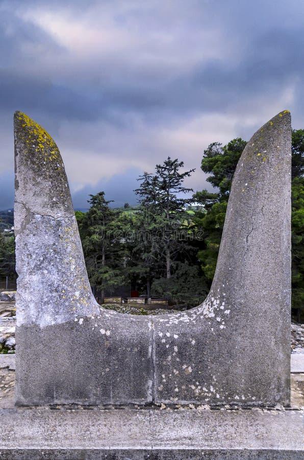 De sakrala tjurhornen skulpterar symbol av makt för Minoansen bredvid den södra Propylaeum byggnaden på den arkeologiska platsen royaltyfri fotografi