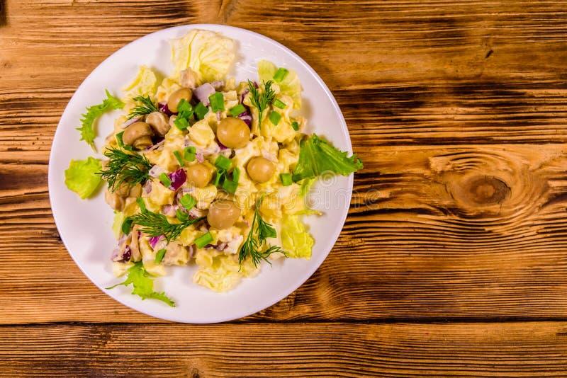 De salade met gemarineerde paddestoelen, eieren, rode ui, kookte aardappel en mayonaise op houten lijst Hoogste mening royalty-vrije stock afbeeldingen