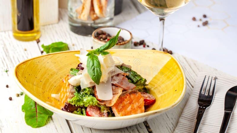 De Salade van Caesar met Zalm mengeling van salades, kersentomaten, parmezaanse kaaskaas, basilicum Een schotel in een ceramische royalty-vrije stock afbeeldingen