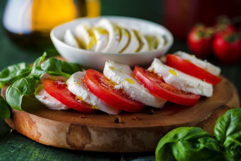 De salade van Caprese Mozarellakaas, tomaten en de bladeren van het basilicumkruid royalty-vrije stock afbeelding